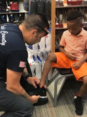 St. Lucie County Firefighters helped kids pick out shoes at two Payless Shoes stores.