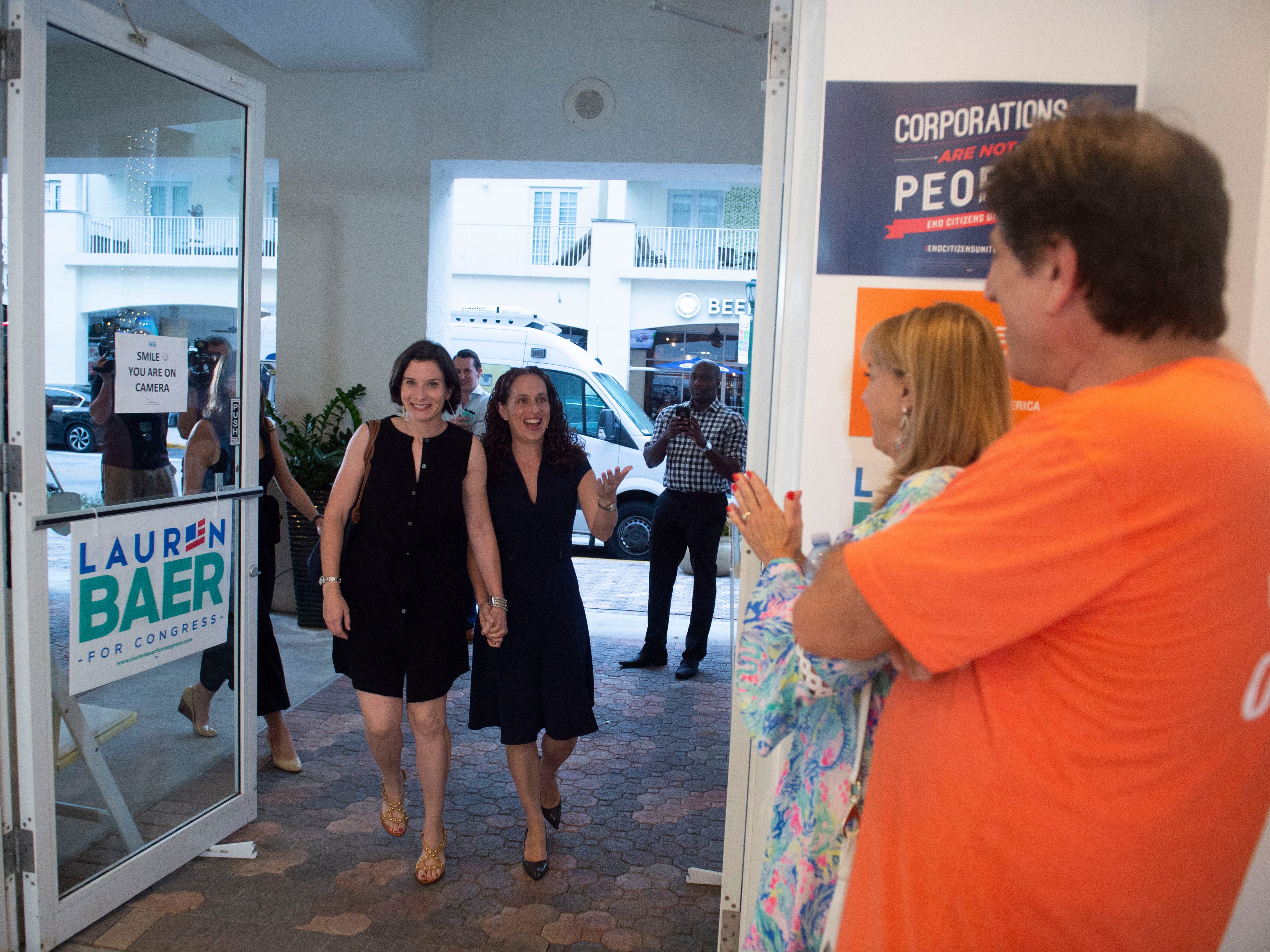 Democrat Lauren Baer, of Palm Beach Gardens, arrives to her primary election night party with wife Emily Meyers on Tuesday, Aug. 28, 2018 at her campaign office in Jupiter. Baer beat challenger Pam Keith in the in the U.S. House District 18 race. Baer, a former Obama administration foreign policy advisor, will be facing incumbent U.S. Rep. Brian Mast in the Nov. 6 general election.