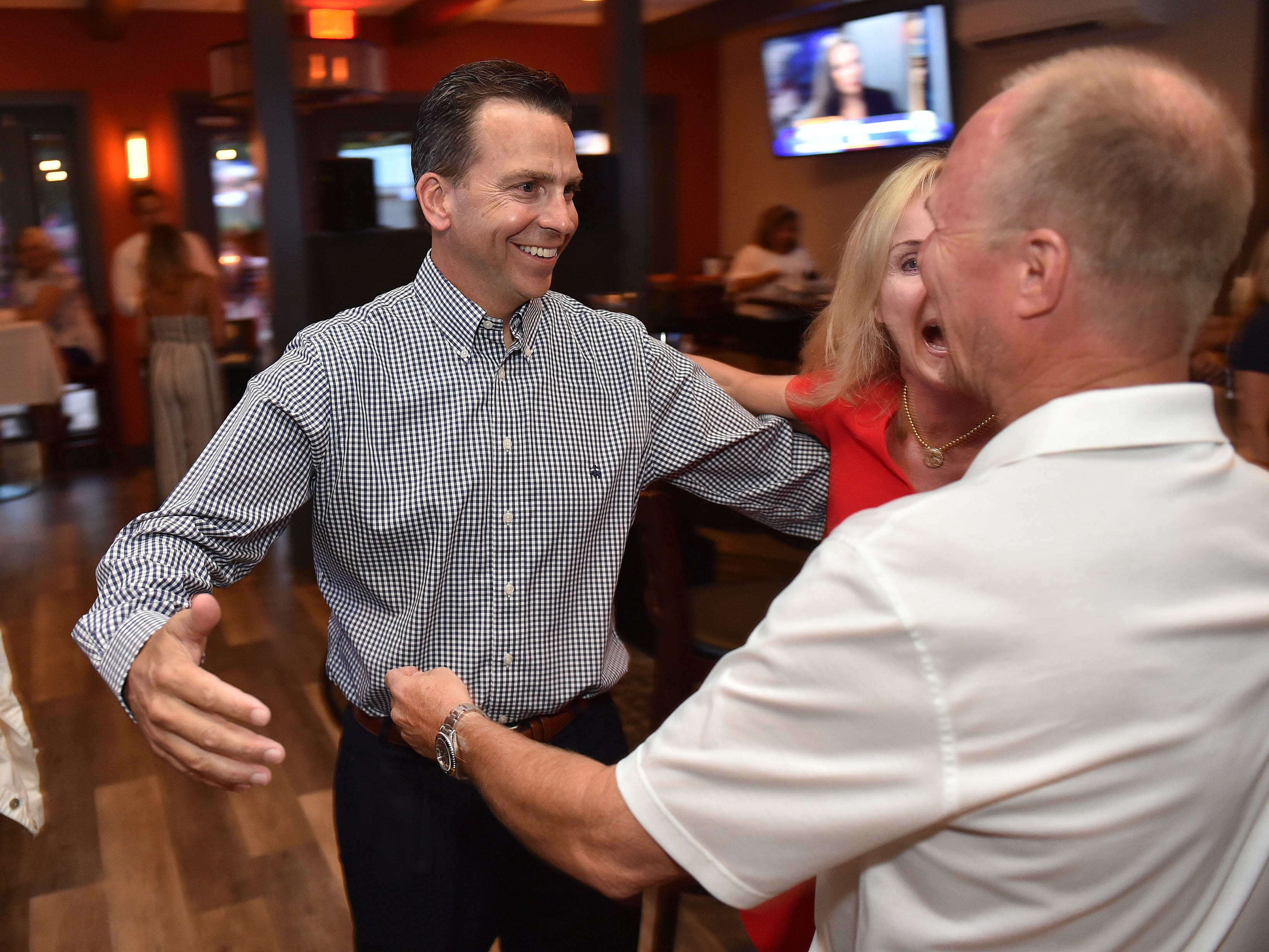 """Toby Overdorf (from left) and his wife Maggie are greeted by supporter John Leighton as they celebrates Overdorf's win over Sasha Dadan in the Florida House District 83 Republican primary at the Talk House in Stuart on Tuesday, Aug. 28, 2018. Overdorf will face Democrat Matt Theobald, a Jensen Beach teacher, in the Nov. 6 general election for the two-year seat that represents parts of Martin and St. Lucie counties, currently held by Republican Rep. Gayle Harrell. """"I'm so grateful for all the support that we have from our community, and from the folks that have come out right and left to help us and support us throughout Martin and St Lucie,"""" Toby Overdorf said. """"I'm really looking forward to the general (election)."""""""