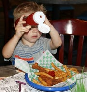 Crew Mahoney makes sure he has plenty of ketchup on his chicken fingers and French fries at Mulligans.