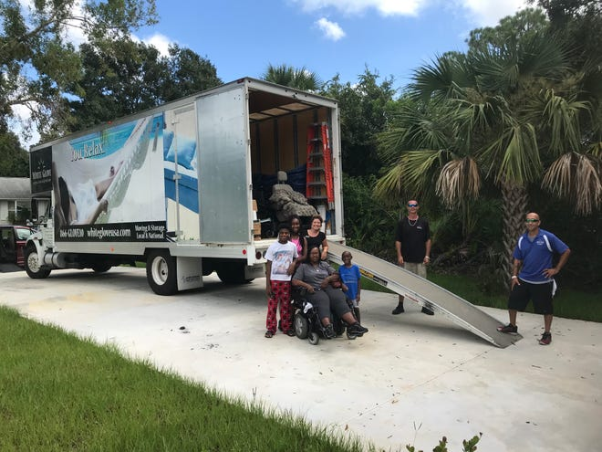 Passion Burgess with kids and White Glove Moving team members Anna Valencia Tillery, Chris Falke, and Terry Stevenson the the new house.