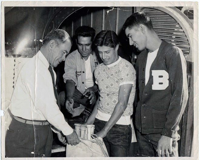 Former Bowie baseball coach Nemo Herrera, left, and Ruben Rodriguez check out a bag of bats. Tony Lara is at far right.