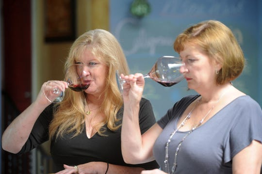 Kristen Shubert, left, a sommelier and owner of VinTura Tasting Room & Wine Rack in downtown Ventura, and Lisa Stoll, a sommelier and owner of the Camarillo-based tour company Explore Wines, demonstrate the wine-tasting techniques that helped earn them first place in the U.S. Open Wine Tasting Competition Aug. 11 in Marina Del Rey. The women will represent the U.S. during the World Wine Tasting Competition from Oct. 12-13 in France.