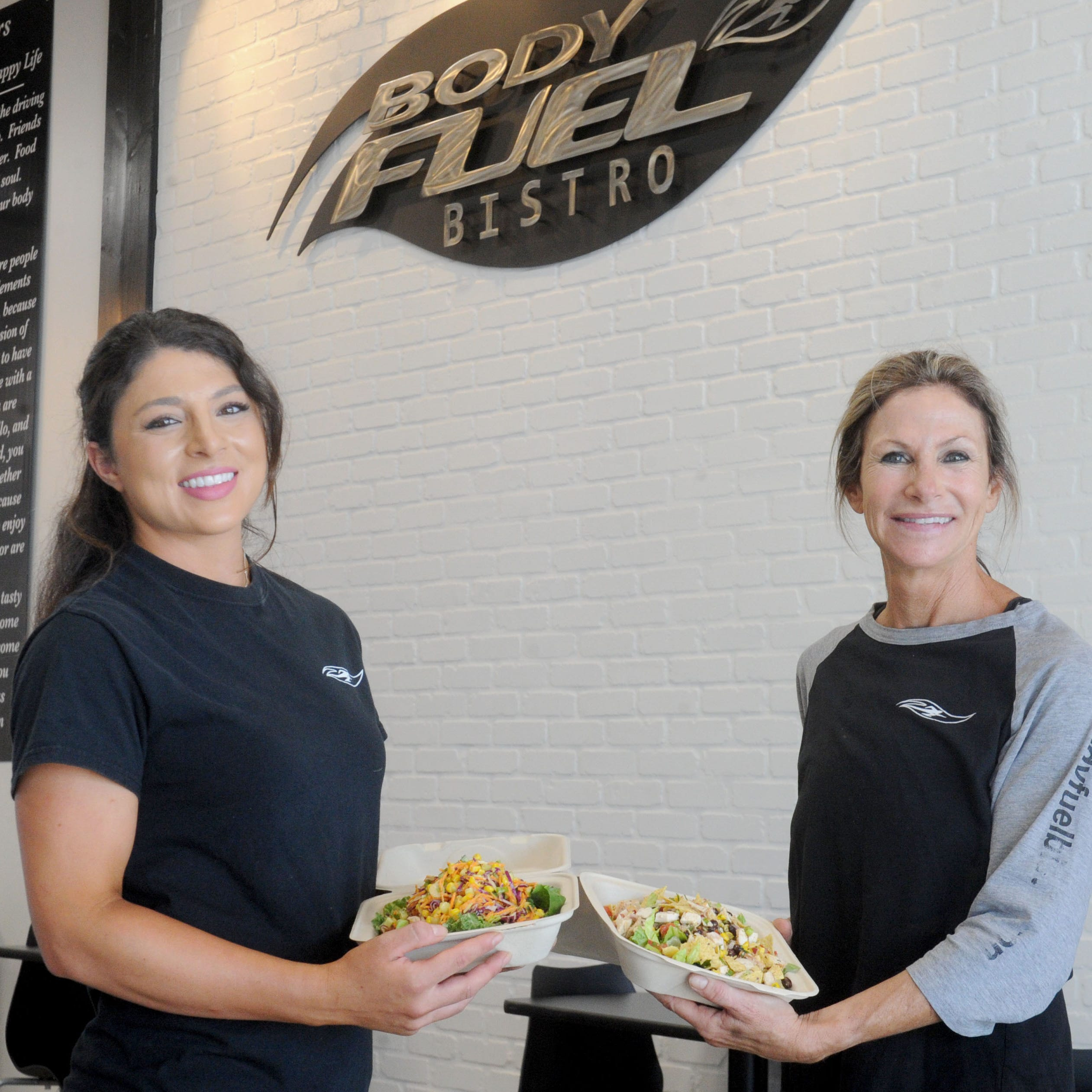 Hailey Wiggins, left, and her mother, Angie Wiggins, pose with salads-to-go at Body Fuel Bistro, their restaurant in Port Hueneme. Specializing in healthy fast food, the bistro will mark its first anniversary on Sept. 22, then participate in The Star's Wine & Food Experience featuring celebrity chef Graham Elliot Nov. 10 in Camarillo.