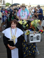 Marie Wright leads as Paul Jankovic pushes a coffin down the boardwalk as the Bethany Beach Jazz Funeral proceeds down the boardwalk in 2011.