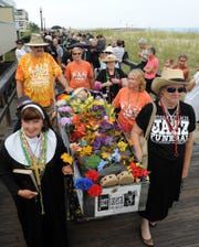 """Sister"" Marie Wright (left) moves a casket down the Bethany Beach boardwalk during the town's annual jazz funeral in 2013."