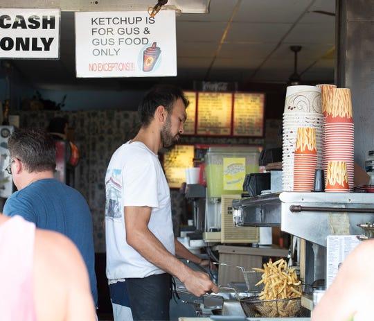 Abrorjon Abdulazimov prepares fries at Gus & Gus in Rehoboth Beach.