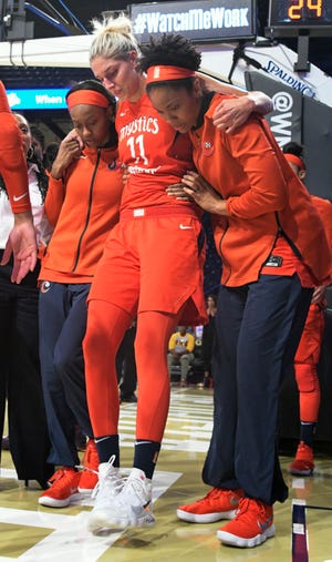 Washington Mystics guard Elena Delle Donne is helped up by fellow players and taken out of Game 2 of a WNBA semifinals basketball playoff after going down against the Atlanta Dream during the second half, Tuesday, Aug. 28, 2018, in Atlanta.