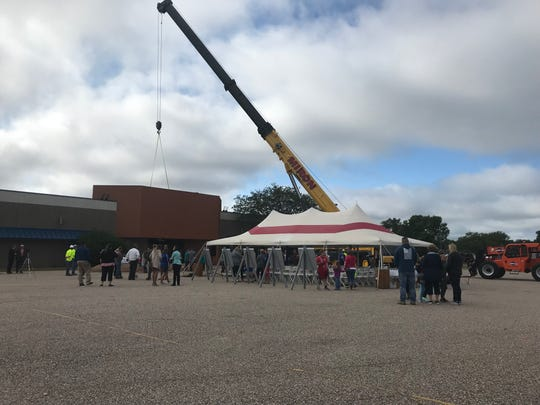 People beginning to gather for the groundbreaking ceremony at the site of the former Rapids Mall, celebrating the beginning of construction for a new YMCA and Boys & Girls Club.