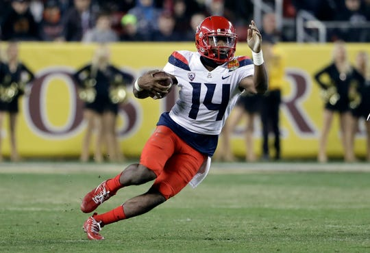 FILE - In this Dec. 27, 2017, file photo, Arizona quarterback Khalil Tate runs against Purdue during the second half of the Foster Farms Bowl NCAA college football game in Santa Clara, Calif. As a versatile quarterback who can beat defenses with his arm and legs, Tate fits the profile of many other recent Heisman winners. (AP Photo/Marcio Jose Sanchez, File)