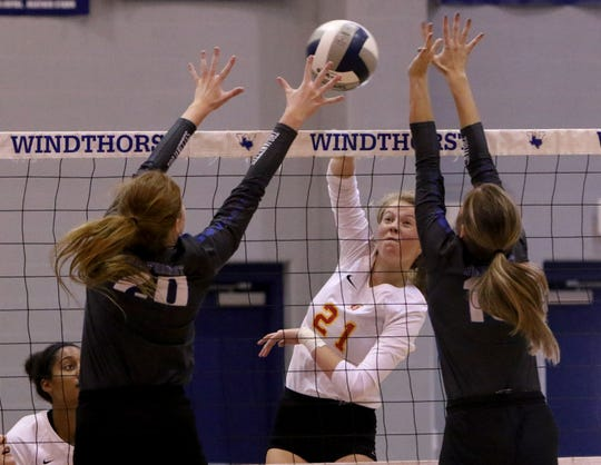 Christ Academy's Morgan Brasher spikes the ball by Windthorst's Brynlee Wolf and Lainey Hughes Aug. 28, 2018, in Windthorst.