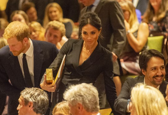 """Prince Harry and Duchess Meghan of Sussex sat next to """"Hamilton"""" creator Lin-Manuel Miranda at the gala performance at Victoria Palace Theatre on Aug. 29, 2018, in London."""