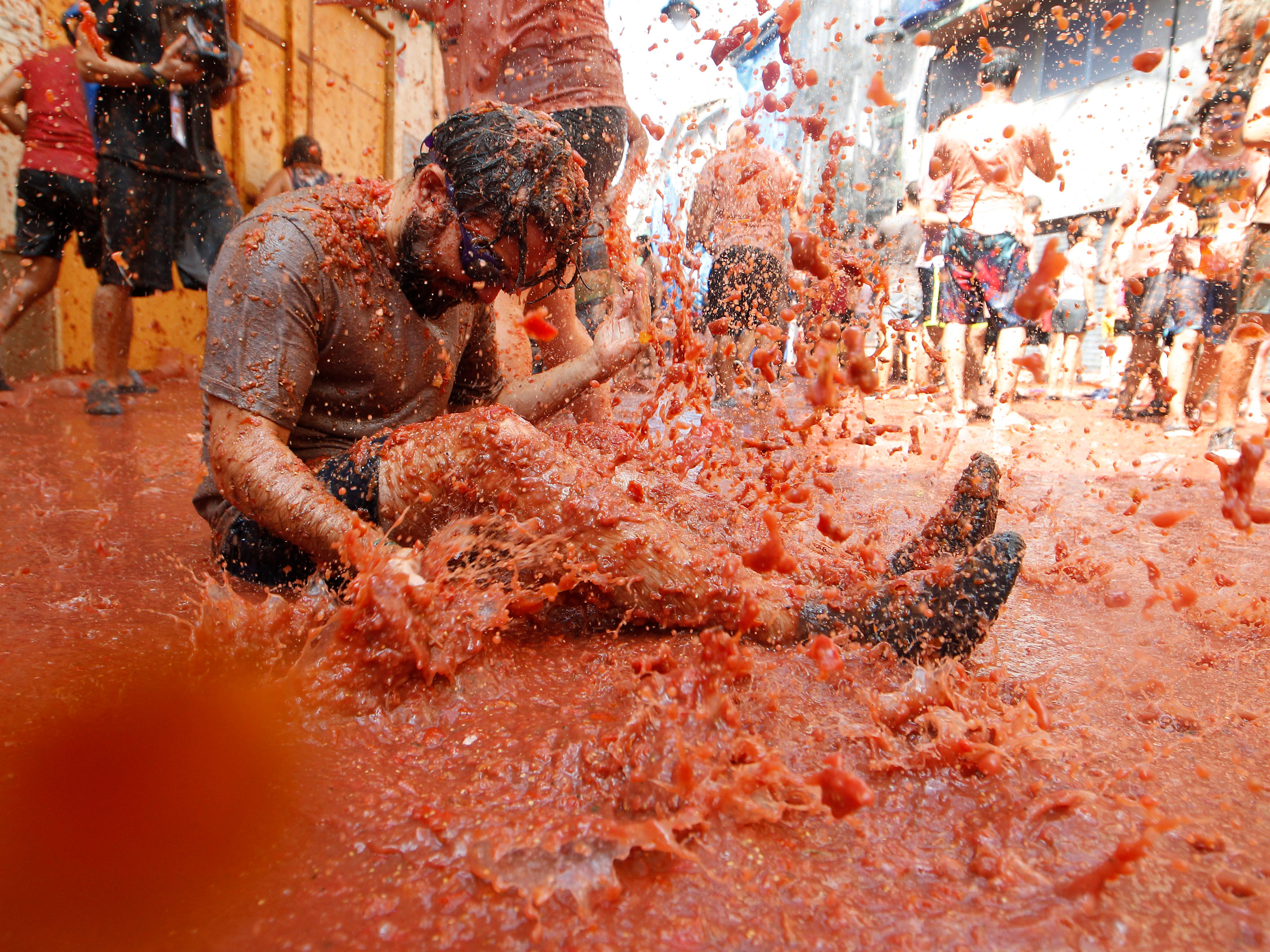 A participant endures being pelted by tomatoes during the annual Tomatina in Bunol, Spain, Aug. 29, 2018.