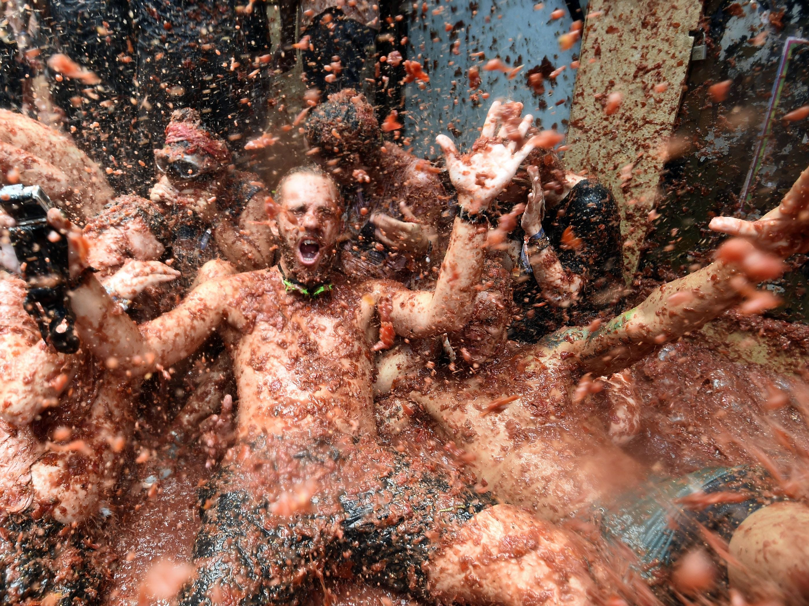 Revelers are pelted with tomatoes as they lie on a tomato puree covered street during the Tomatina festival in Bunol, Spain, Aug. 29, 2018.