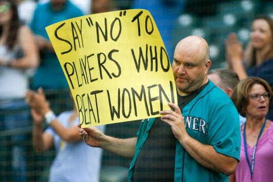A Mariners fan makes his opinion on the Astros' decision to sign closer Roberto Osuna clear before a game in Seattle.