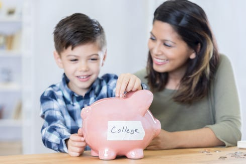 Cheerful Asian boy smiles while placing coins in a piggy bank. His mother is teaching him about saving for his education. A label on the piggy bank reads 'college.'