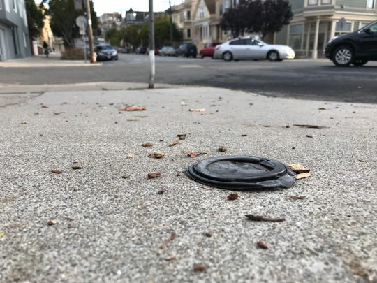 A plastic cup lid discarded on a sidewalk in San Francisco, near a storm drain. When the rains come, if the lid is not picked up and ends up in a trash can, it could easily be washed into the storm drain and from there, potentially out to sea.