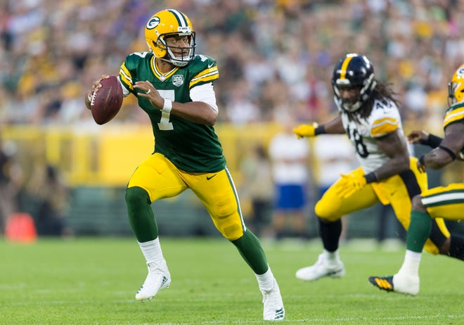 Green Bay Packers quarterback Brett Hundley (7) scrambles with the football under pressure from Pittsburgh Steelers linebacker Bud Dupree (48) during the first quarter at Lambeau Field.