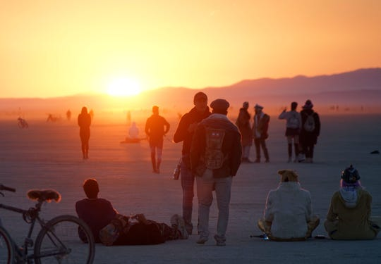 Burning Man attendees watch the morning sun clear the horizon after dancing all night.