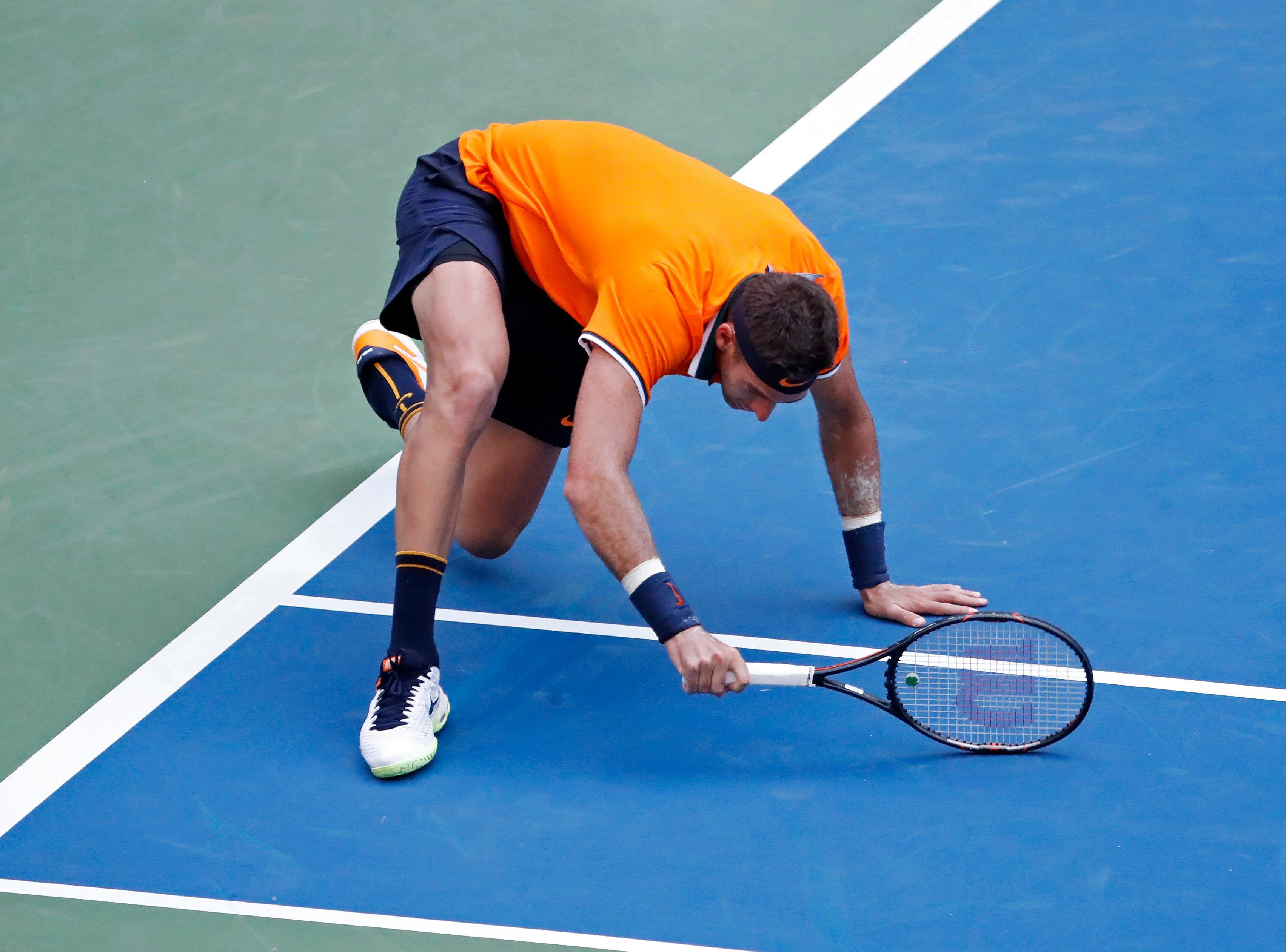 Juan Martin del Potro slips after hitting a forehand against Denis Kudla.