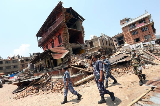Nepalese police and army personnel inspect damage to houses in the aftermath of the powerful earthquake in Sankhu on the outskirts of Kathmandu, Nepal, on May 21, 2015.