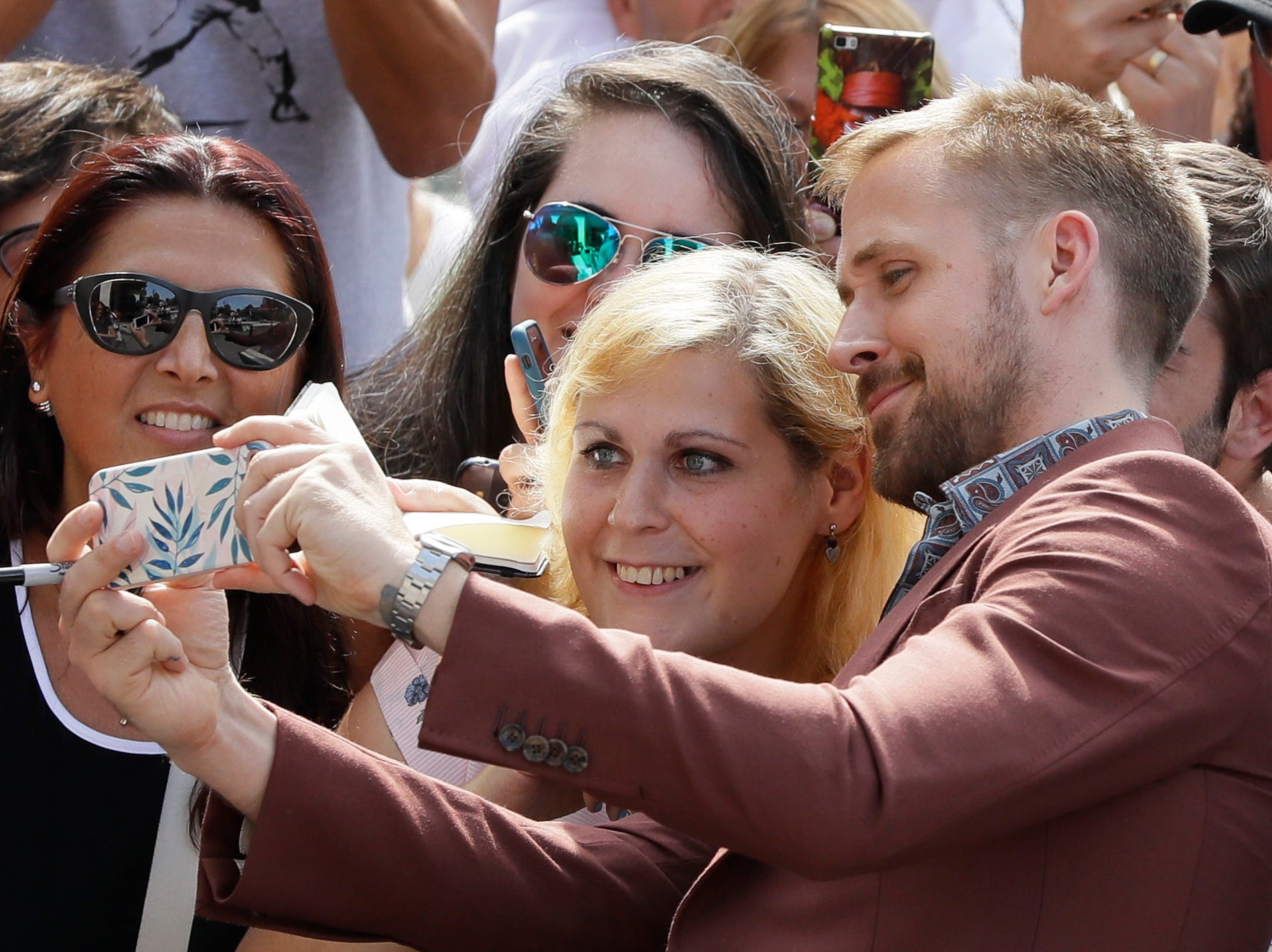 Actor Ryan Gosling poses for photographs with fans upon arrival for the photo call of the film 'First Man' at the 75th edition of the Venice Film Festival in Venice, Italy, Wednesday, Aug. 29, 2018. (AP Photo/Kirsty Wigglesworth) ORG XMIT: LENT139
