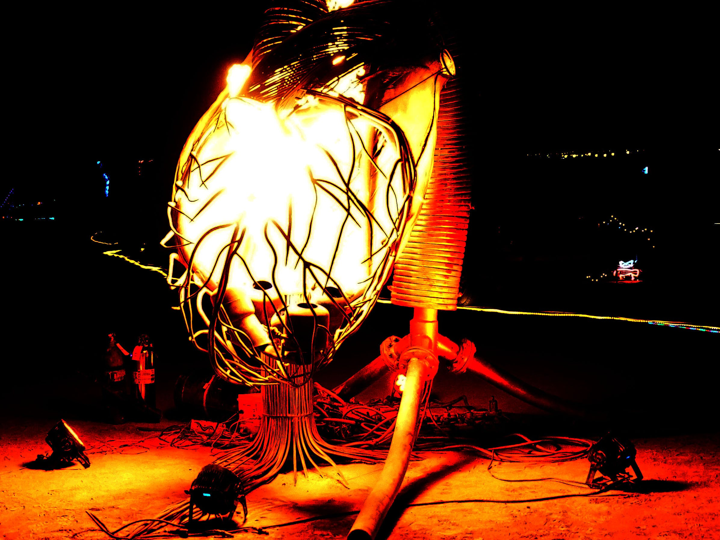 A giant metal heart glows from fire within at Burning Man.