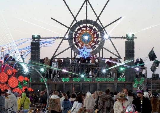 Hundreds of dancers crowd in front of the Mayan Warrior, a bus-sized mobile music stage at Burning Man.