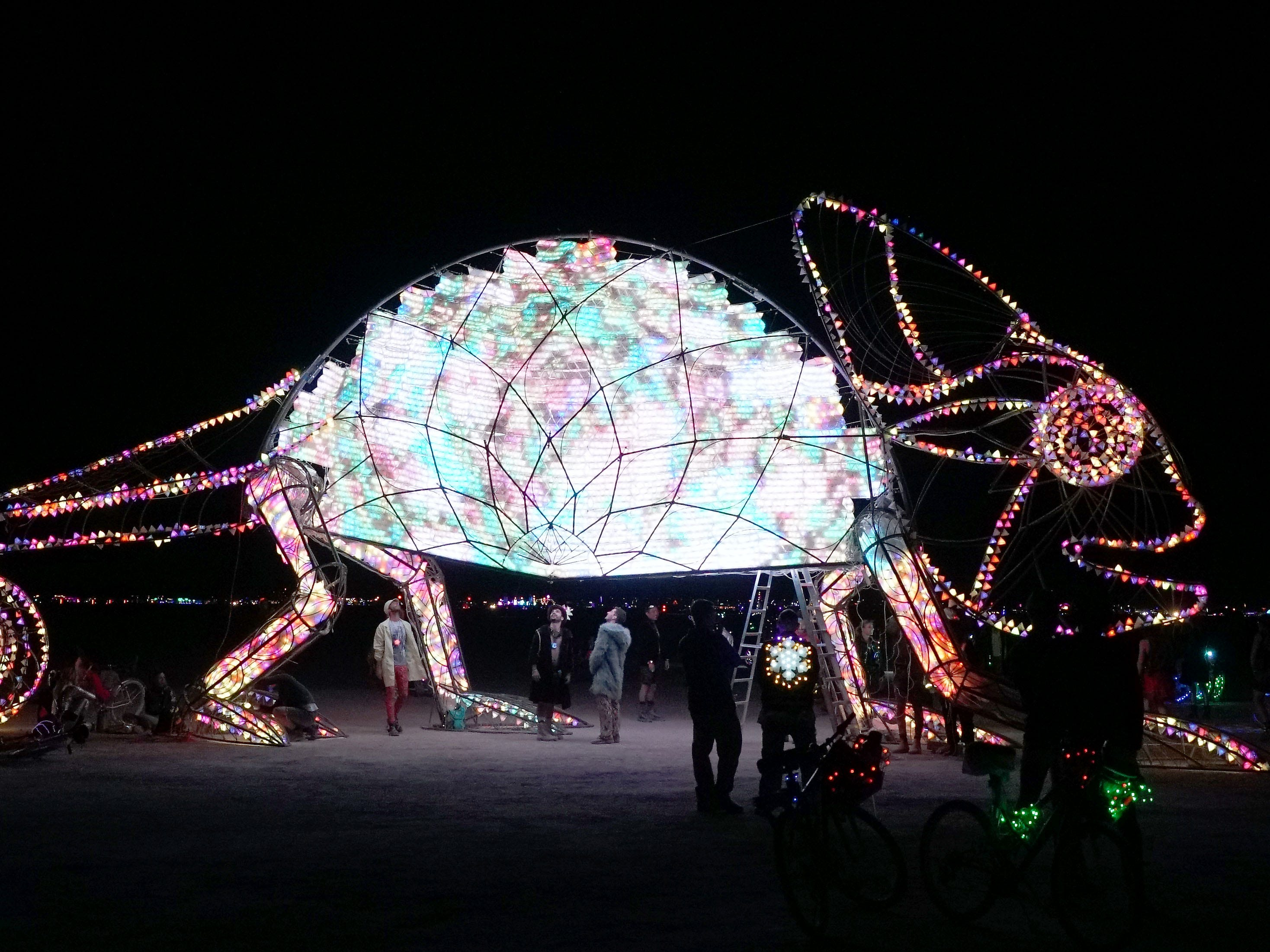 Burning Man attendees walk beneath an illuminated chameleon late at night.