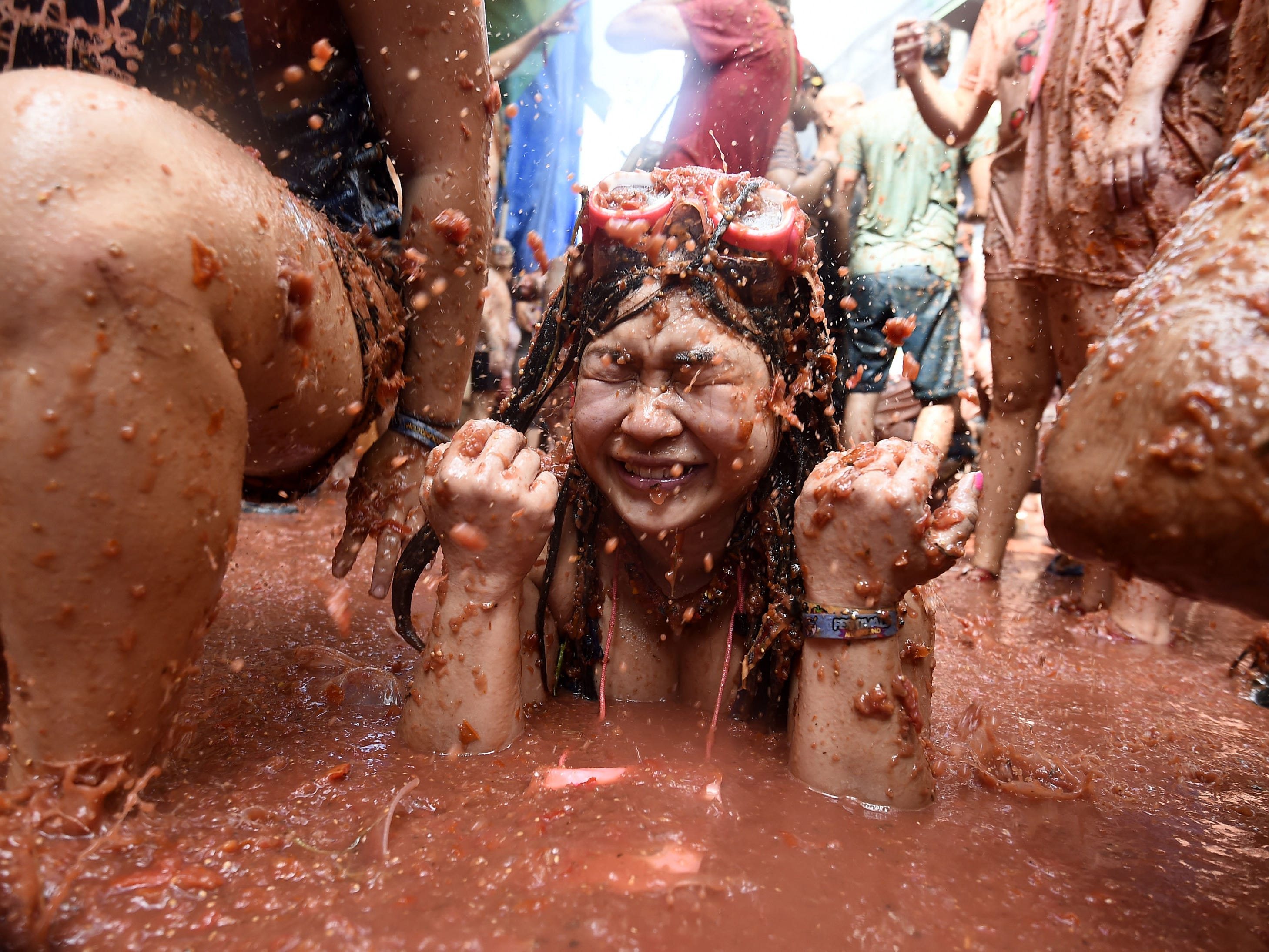 A participant is pelted with tomatoes as she sits in a smashed tomato puree puddle during the Tomatina festival in Bunol, Spain, Aug. 29, 2018.