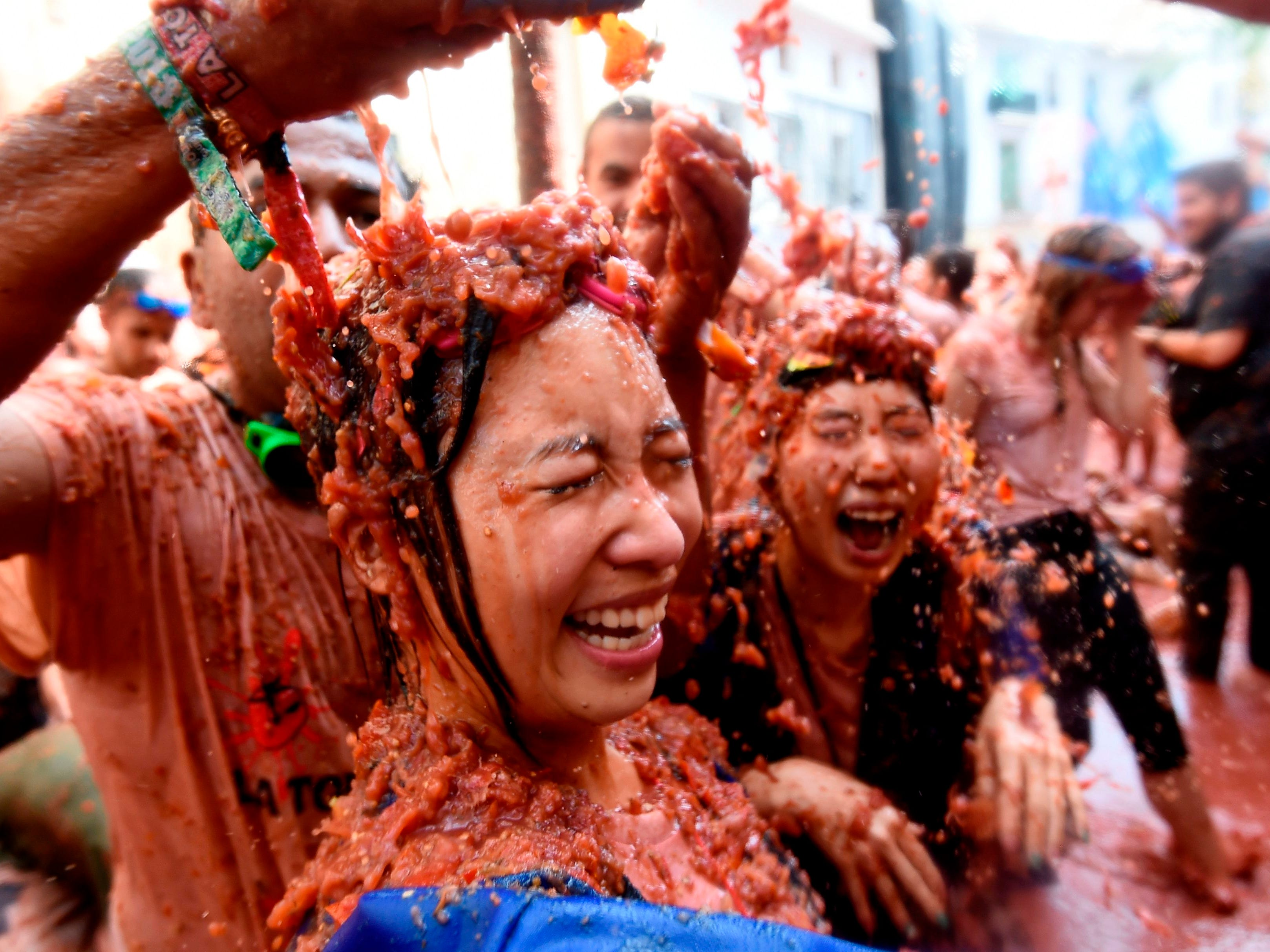 """Revelers are covered with smashed tomatoes during the Tomatina festival in Bunol, Spain, Aug. 29, 2018. The iconic annual fiesta that takes place on the last Wednesday of August and celebrates its 73rd edition has been billed as """"the world's biggest food fight"""" becoming a major draw for tourists."""