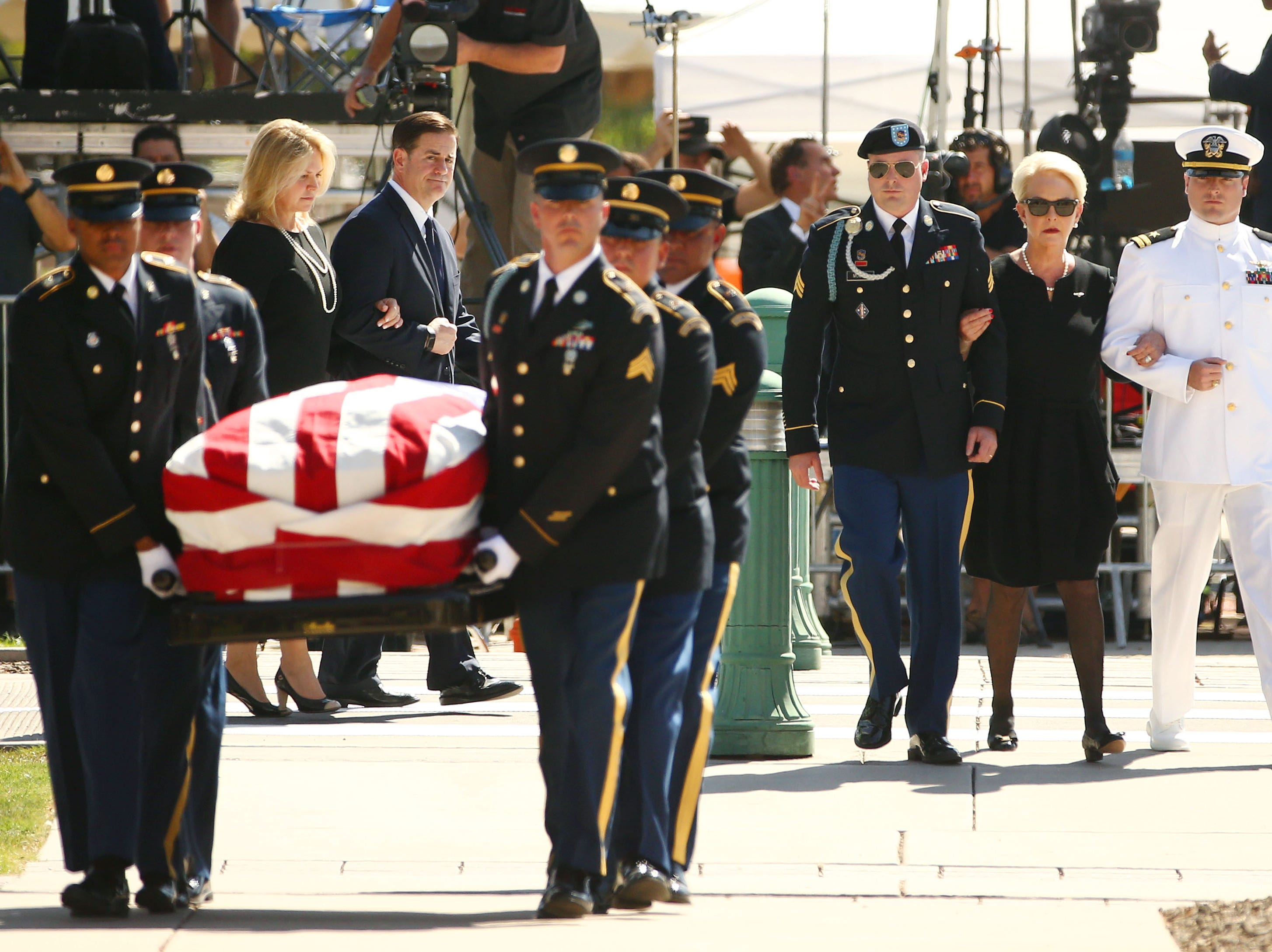 Mrs. Cindy McCain is escorted by her sons, Jimmy McCain and Jack McCain, and Arizona Gov. Doug Ducey and First Lady Angela Ducey, left, as they follow the casket of U.S. Sen. John McCain for his memorial service at the Arizona State Capitol.