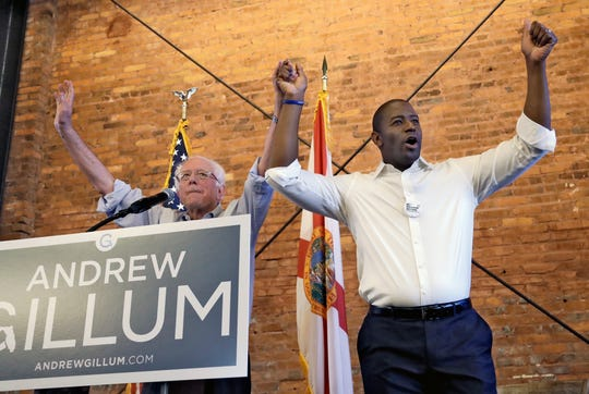 U.S. Sen. Bernie Sanders, I-Vt, left, and Democratic gubernatorial hopeful Andrew Gillum hold hands during a campaign rally Friday, Aug. 17, 2018, in Tampa, Fla. (AP Photo/Chris O'Meara) ORG XMIT: FLCO101
