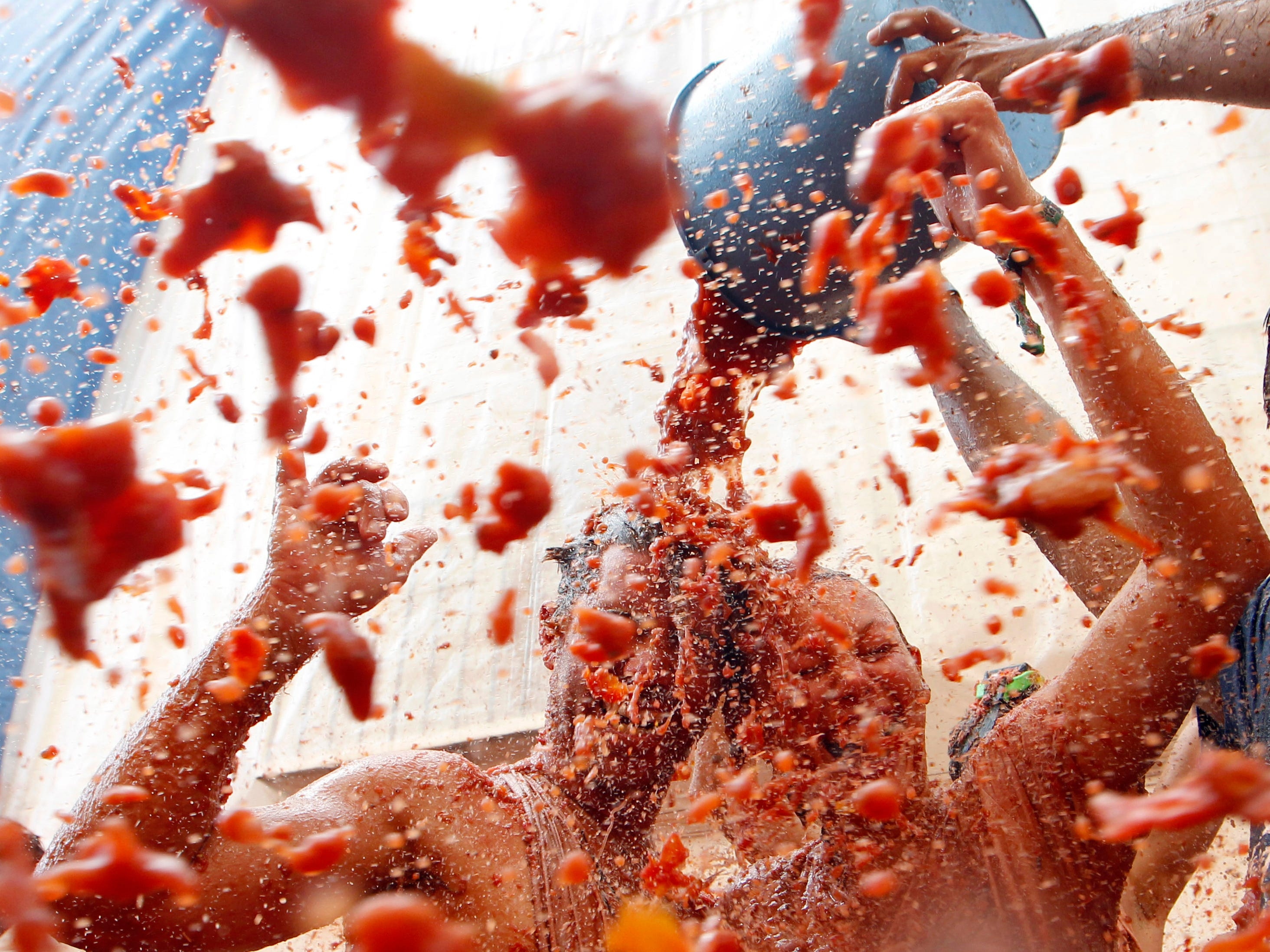 Participants throw tomatoes at each other during the annual Tomatina in Bunol, Spain, Aug. 29, 2018.