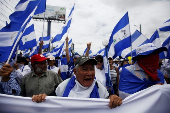 People march in favor of doctors dismissed by the government of President Daniel Ortega in Managua, Nicaragua, on Aug. 4, 2018.