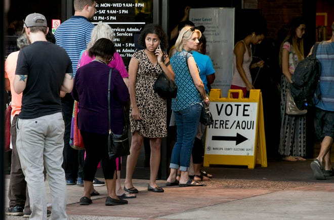 People wait in line to vote in the primary, at the polling place at the Tempe Public Library in Phoenix.