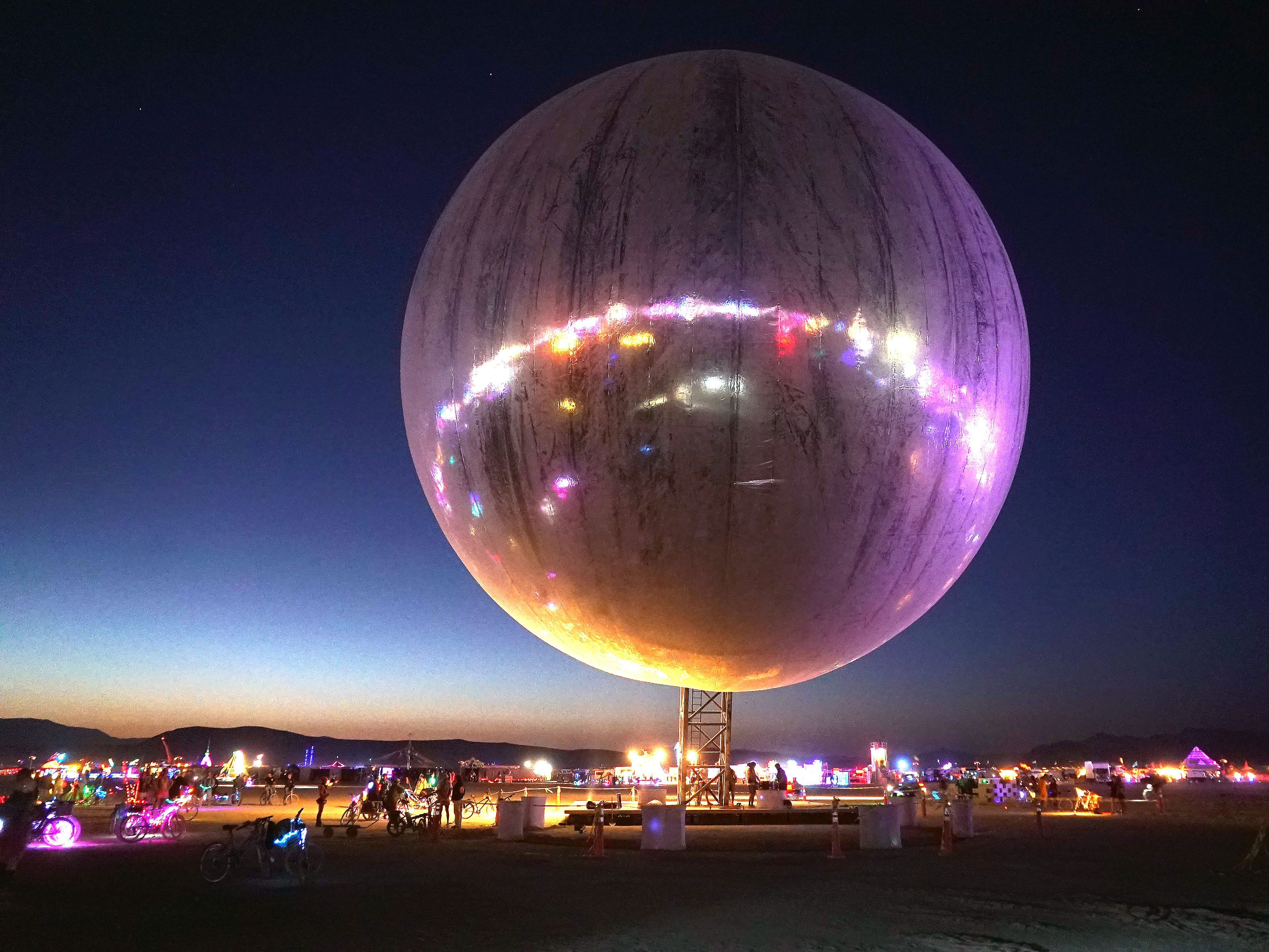 An inflatable sphere covered in reflective material hangs over the dusty playa of Burning Man, reflecting back the neon and LED lights scattered around the area.
