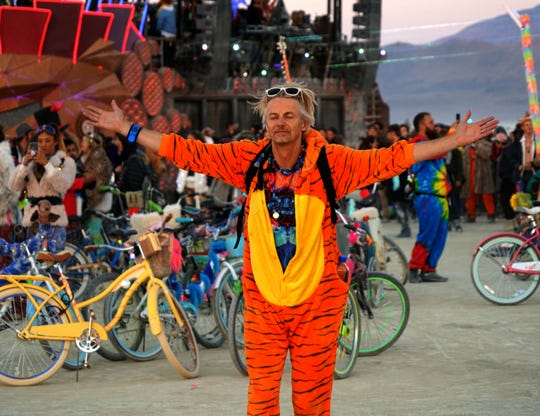 Peter Read of London raises his arms to greet the morning sun at Burning Man after all-night dancing.