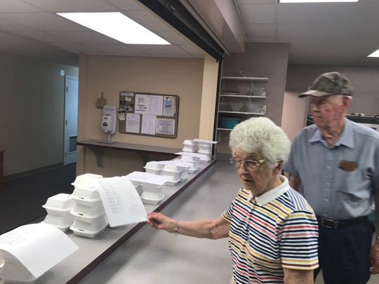 Rosa and Horace Gibson look over the delivery menus at the Pendleton First Baptist Church in the final days of the SOUP Program.