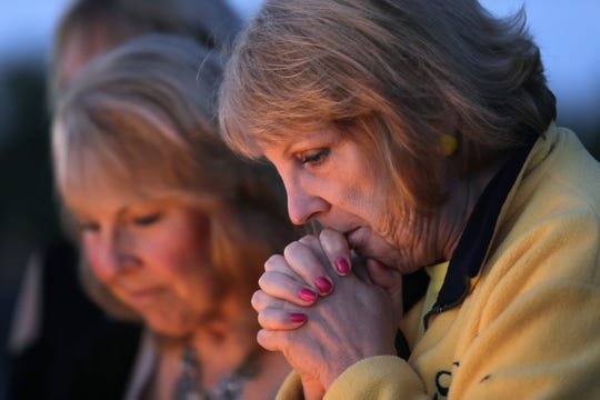 Jeanine Dorow of Neenah says a prayer during an event Wednesday celebrating the lives of Lauren and Cassie Laabs at Waverly Beach in Menasha. Dan Powers/USA TODAY NETWORK-Wisconsin