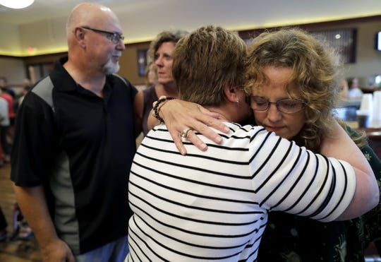 Cheryl Laabs, far right, gets a hug from family friend Debbie Galeazzi of Menasha as her husband, Kim Laabs, far left, is comforted by Mary Fritz of Appleton during an event Wednesday at Waverly Beach in Menasha to celebrate the lives of their daughters, Lauren and Cassie Laabs. Dan Powers/USA TODAY NETWORK-Wisconsin