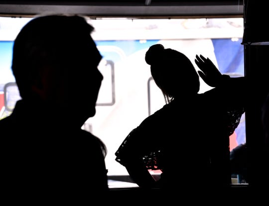 """Listeners outside and within the room are silhouetted against the Ted Cruz campaign van, known as """"The Cruzer,"""" as they listen to Cruz speak at Betty Rose's Little Brisket Thursday. More than 200 crowded the dining room to hear his remarks and ask questions."""