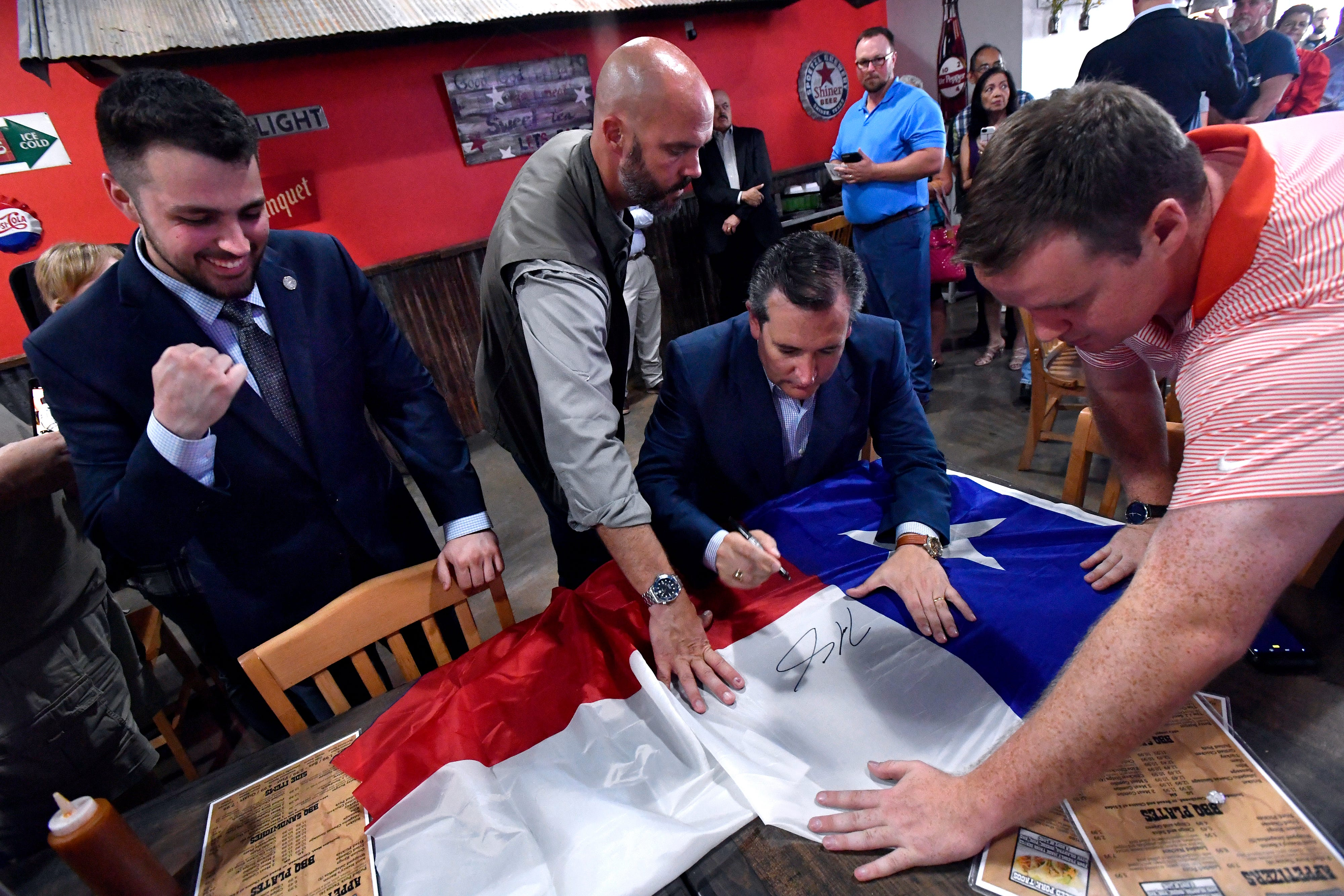 Tyler Hasenjaeger, a student at Abilene Christian University and chairman of the College Republicans, fist-pumps as U.S. Sen.Ted Cruz autographs his Texas flag Aug. 30 at a campaign meet-and-greet at the Catclaw Drive location of Betty Roses' Little Brisket in Abilene.