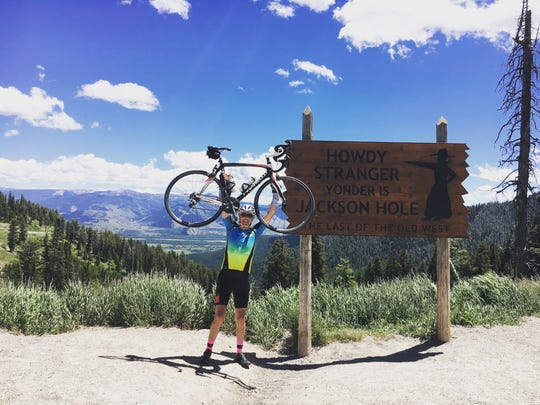 Brad Campbell, of Fairview, lifts his bike in victory after cross the Teton Pass in Wyoming, one of the highlights of his 3,600-mile cross-country bike ride.