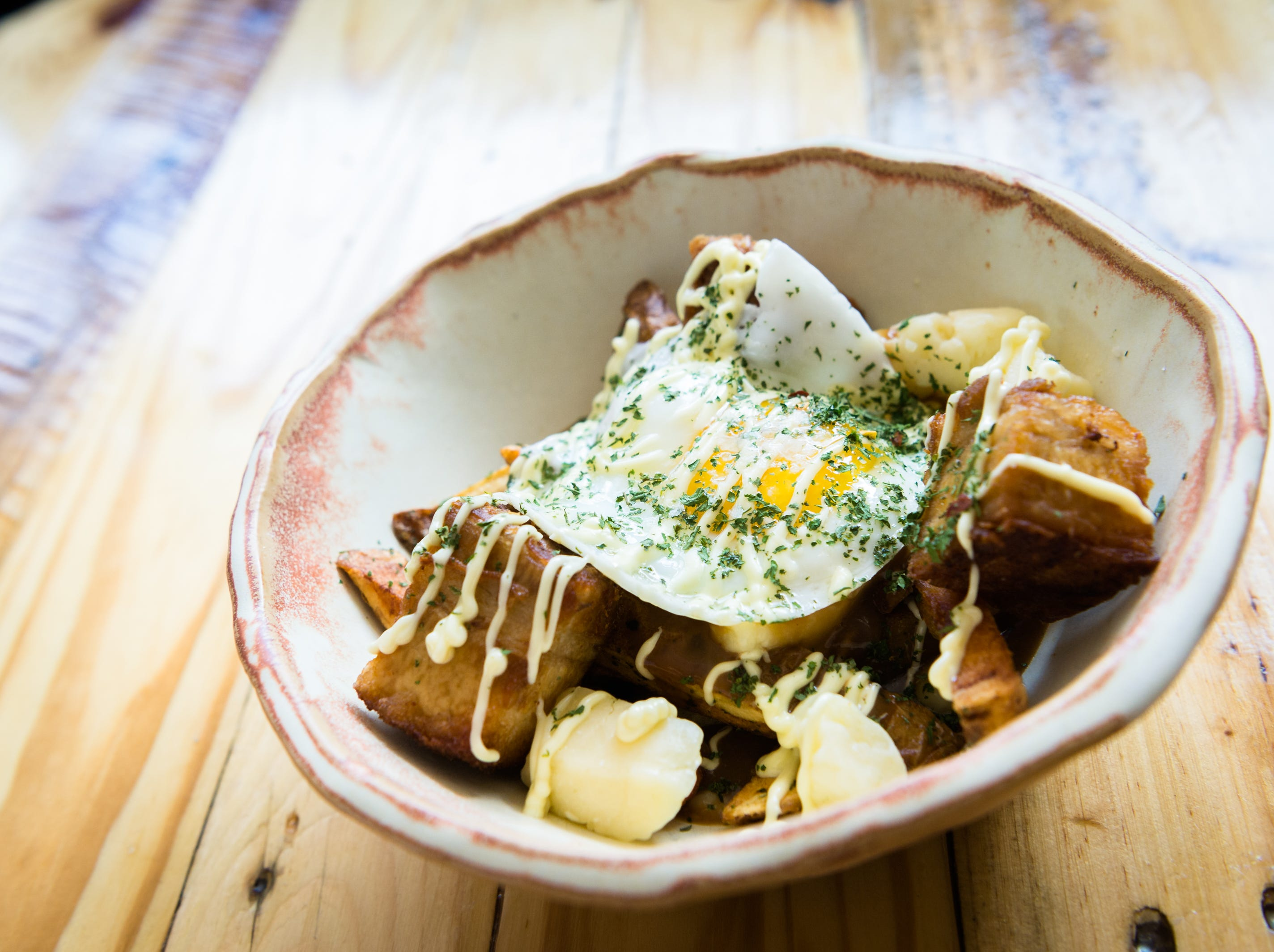 The Good the Bad & the Happy poutine dish with pork belly, truffle mayo, foie gras mousse & gravy, frites, curd, and sunny eggserved at BadHappy Poutine on Merrimon Avenue in Asheville.