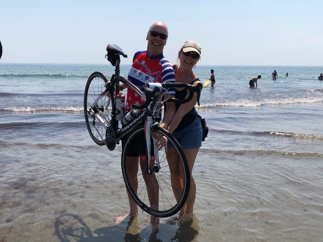 Brad Campbell and his wife, Judyanne, dip the wheel of his bike in the Atlantic Ocean at Wallis-Sands State Beach in Portsmouth, New Hampshire on Aug. 6, the day he finished his 3,691-mile ride across the country.