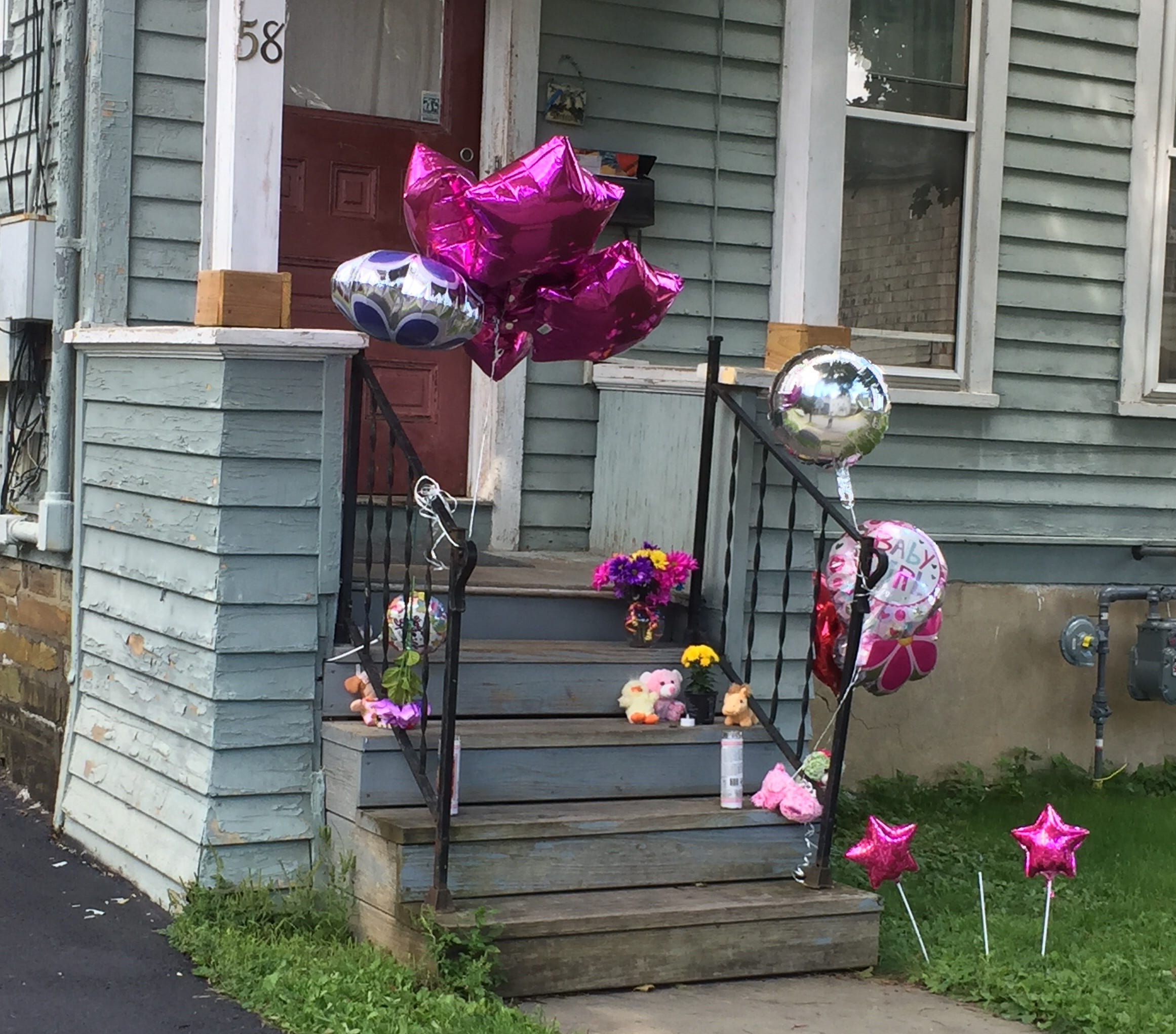Balloons and flowers are placed outside a Henry Street home  in Norwich, where police say a child was assaulted by her father Devan Ellsworth. The 20-month-old girl died Aug. 27, 2018.