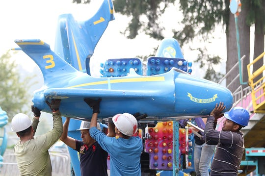A Blue Angel plane is lifted into position during setup at the Kitsap County Fairgrounds last month.
