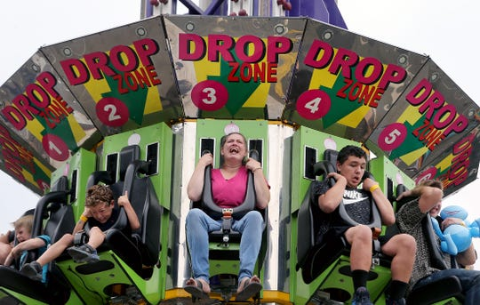Julie Taylor, center, of Bremerton rides on the Drop Zone at the Midway at the Kitsap County Fair & Stampede on Friday, August 24, 2018 at the Kitsap County Fairgrounds.