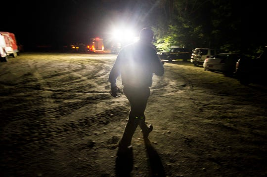 Morristown Fire Chief Shawn Goodell walks to a remote trail head in the foothills near Sterling Mountain late Wednesday night, Aug. 29, 2018, to talk with Vermont State Police officers as dozens of rescuers scoured the mountain for a glider that went missing and was spotted deep in the woods.